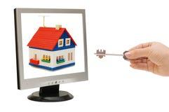 De hand met een sleutel bereikt voor het huis Stock Afbeelding