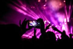 De hand met een smartphone registreert levend muziekfestival, die foto van overlegstadium nemen royalty-vrije stock afbeelding