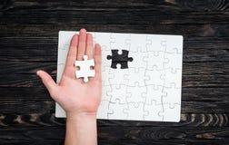 De hand met het laatste stuk van wit uncomleted raadsel Stock Afbeelding