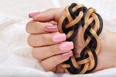 De hand met lange die kunstmatig manicured spijkers met roze nagellak worden gekleurd stock fotografie