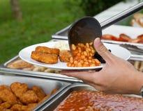 De hand met plastic gietlepel dient gebakken bonen en goudklompjes Royalty-vrije Stock Foto's