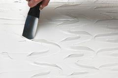 De hand met spatel maakt textuur op wit pleister stock afbeelding