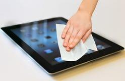 De hand met witte nat veegt tablet het schoonmaken af stock foto