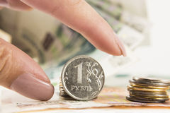 De hand neemt de roebel en de dollars met banken van roebels Stock Afbeelding