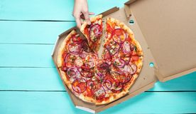 De hand neemt een stuk van pizza stock fotografie