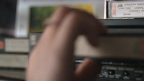 De hand neemt een video van de videospeler en zet dichtbij het stock video