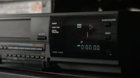 De hand neemt een videocassette, neemt het in de videospeler op en duwt het spel stock footage