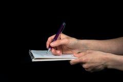 De hand neemt nota's over een blocnote op een zwarte achtergrond stock foto's