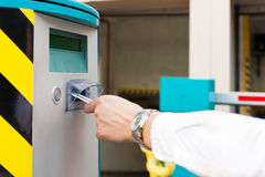 De hand neemt parkerenkaartje in barrière van g op Stock Fotografie