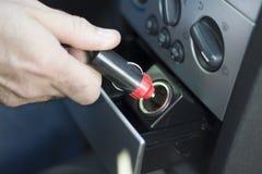 De hand neemt de stop in de 12V contactdoos van de auto` s aansteker op Stock Foto's