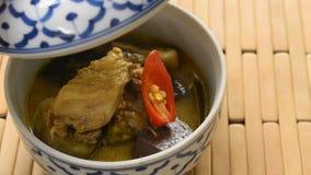 De hand opende dekking van gekookte kip met aubergine in groene kerrie op kom stock footage