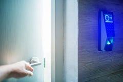De hand opent de deur met het toegangsbeheersysteem van het vingeraftasten bij veilige ruimte te openen Onscherp beeld stock afbeelding