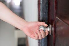 De hand opent de deurknop stock afbeeldingen
