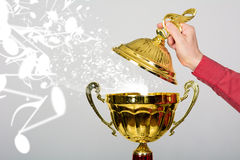 De hand opent het deksel van de gouden kop met een muzikale sleutel royalty-vrije stock afbeeldingen