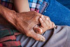 De hand raakt en houdt een oude mens gerimpeld Stock Afbeelding