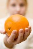 De hand rekt een sinaasappel uit stock foto