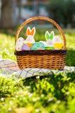 De hand schilderde paaseieren en konijntje in grote rotanmand op groen gras op witte handdoek Traditionele decoratie voor Pasen stock afbeelding