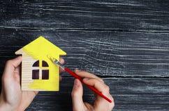 De hand schildert binnen een huis aan gele kleur Concept reparatie, hobby, het werk Reparatie en het schilderen van blokhuisbeeld stock fotografie