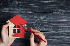 De hand schildert binnen een huis aan rode kleur Concept reparatie, hobby, het werk Reparatie en het schilderen van blokhuisbeeld royalty-vrije stock fotografie
