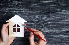 De hand schildert een huis Concept reparatie, hobby, het werk reparatie stock fotografie