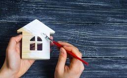 De hand schildert een huis Concept reparatie, hobby, het werk Reparatie en stock foto