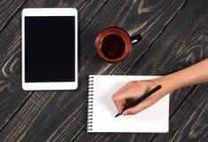 De hand schrijft een zwarte pen in een witte blocnote Royalty-vrije Stock Foto's