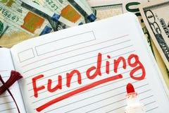 De hand schrijft Financiering in een nota stock fotografie