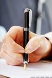 De hand schrijft met een pen in een notitieboekje Stock Foto's
