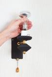De hand schroeft gloeiende lightbulb in een lamp op witte muur los Royalty-vrije Stock Afbeeldingen