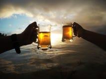 De hand silhouetteert holdingsbieren in de glazen terwijl zonsondergang Stock Afbeelding