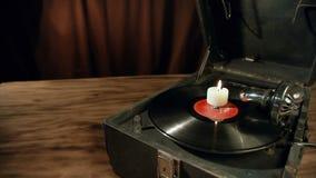 De hand steekt een kaars aan die zich op de retro grammofoon bevindt stock video