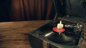 De hand steekt een kaars aan die zich op de retro grammofoon bevindt stock footage