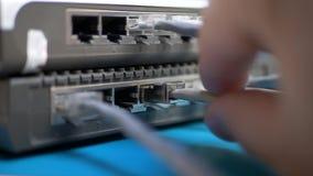 De hand stopt ethernet kabel in router stock videobeelden