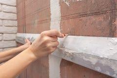 De hand trekt een horizontale lijn met een potlood op de muur gebruikend aluminiumregel royalty-vrije stock afbeeldingen