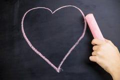 De hand trekt een roze krijthart stock foto's