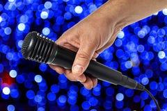 De hand trekt een zwarte microfoon op een multi-colored achtergrond Close-up royalty-vrije stock fotografie