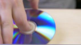 De hand trekt de schijf van de doos en neemt aan dvdspeler op stock footage