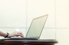 De hand typt op laptop op houten lijst aangaande witte vensterbank Stock Fotografie