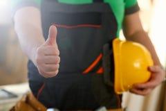 De hand van arbeider in gele helm toont bevestig stock foto's
