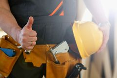 De hand van arbeider in gele helm toont bevestig royalty-vrije stock afbeeldingen