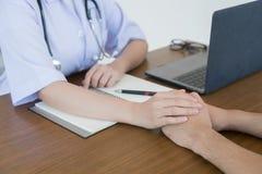 De hand van de arts maakt de mannelijke patiënt zeker stock fotografie