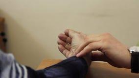 De hand van arts met klok controleert impuls van patiënt in kliniek stock video