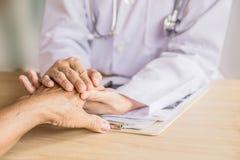 De hand van de artsenholding en troostende oude patiënt in het ziekenhuis stock foto