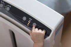 De hand van de baby het drukken de machtsknoop op de luchtzuiveringsinstallatie om de verontreinigde lucht te schoonmaken stock afbeelding