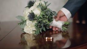 De hand van de bruidegom neemt een huwelijksboeket dat op de lijst naast de trouwringen legt stock footage