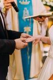 De hand van de bruidegom zet de trouwring op de vinger van de bruid Royalty-vrije Stock Afbeelding