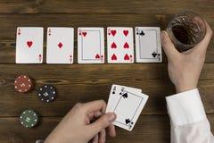 De hand van de de chipkaartalcohol van pook, houten achtergrond, een glas en een wit overhemd stock foto's