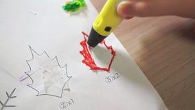 De hand van de close-upjongen gebruikt een 3D pen Hij creeert een installatieblad van rood ABS plastiek stock footage