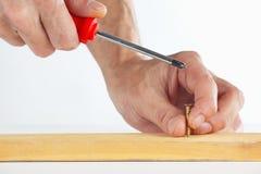 De hand van de arbeider die de schroef in een houten blok aanhalen royalty-vrije stock foto