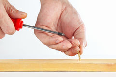 De hand van de arbeider verdraait de schroef in een houten blok stock fotografie